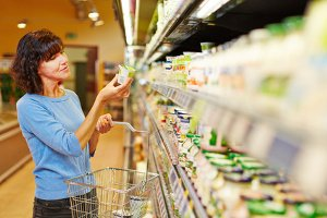 Ältere Frau mit Einkaufskorb kauft Joghurt im Supermarkt